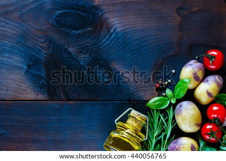 Dark wooden table with spices and vegetables. Organic vegetables. Vegetarian food. Background layout with free text space. Dark rustic style. - stock photo