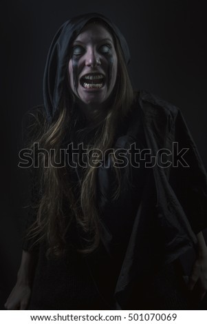 Dark zombie woman, horror girl with scary expression and grim look on her face, halloween concept