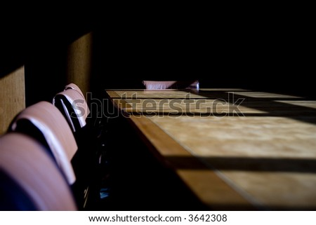 Darkened boardroom with heavy shadows, cold and uninviting and empty seats
