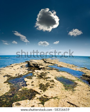 Darkening storm cloud with silver lining from sun above rocky shoreline beside sea in Fife, Scotland. - stock photo