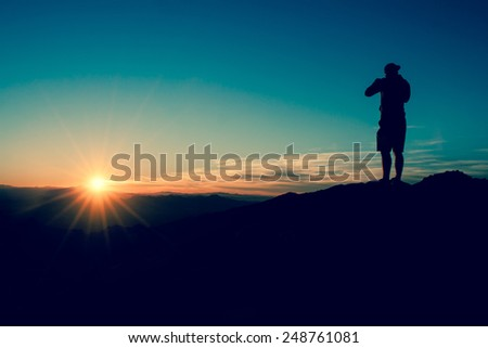 Darkness Closing - Natural Dusk Theme, Mountain View with Silhouette of a Male Standing in the Top of a Hill at Sunset - stock photo