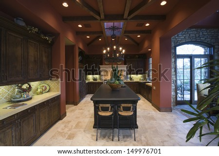 Darkwood and beamed ceiling in modern and spacious kitchen at home - stock photo