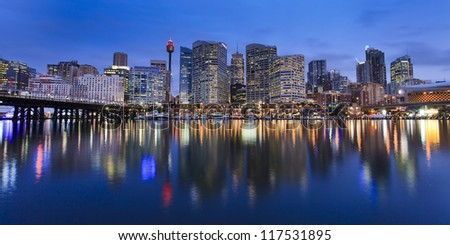 Darling Harbour bay in Sydney city panoramic view at sunset with lights illuminated in water over boats