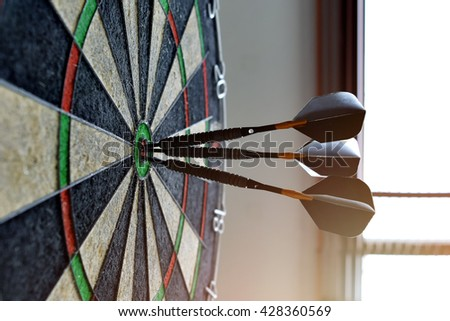 dart arrow concept , target dart with target arrows over sunray background , to target marketing or target arrow concept . - stock photo