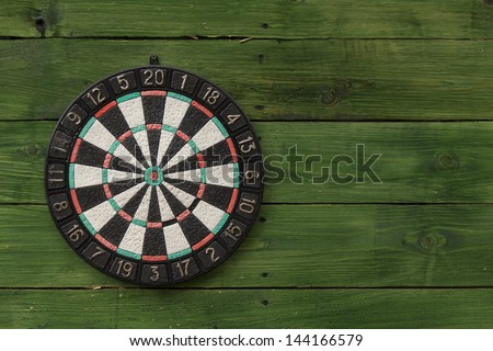 Dart board on a green wooden wall - stock photo