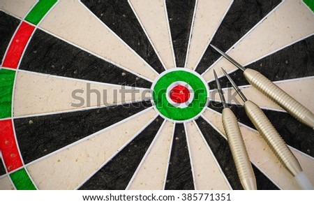 Dart board showing bullseye with three darts.