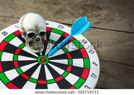Dart board with a blue arrow and humen skull placed on wooden background. Failure of thought and success hitting target aim goal achievement concept background. - stock photo