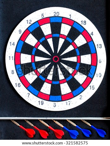Dart board with 3 red darts and 3 blue darts - stock photo