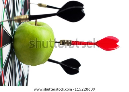 dart hit green apple in the target center - stock photo