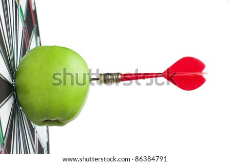 dart hit green apple in the target centre - stock photo