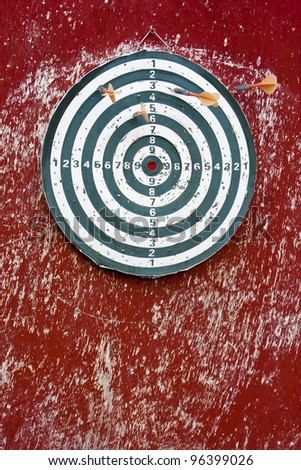Dart hitting a target on red - stock photo