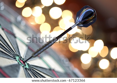 Dart in bulls eye of dartboard with shallow depth of field concept for hitting target - stock photo