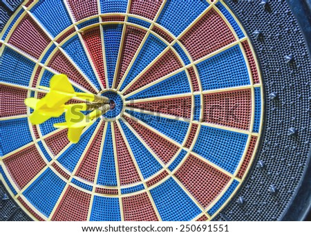 Dart in bulls eye three times of dartboard - stock photo