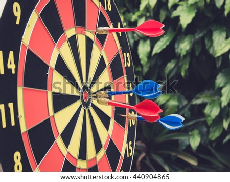 Dart is a competition and opportunity. Dartboard is be like as the target center and goal of business. therefor Bulls eyes of Dart board is both challenge,success,risk management,goal,opportunity. - stock photo