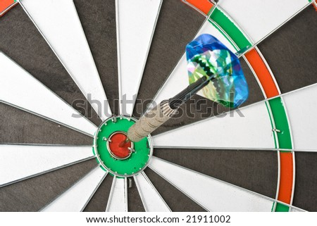Dart on bull's eye of a dartboard. Close up.