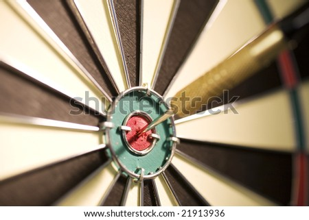 Dart on bull's eye of a dartboard. Close up. - stock photo