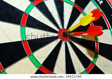 Dart on bull's eye of a dartboard. Close up view