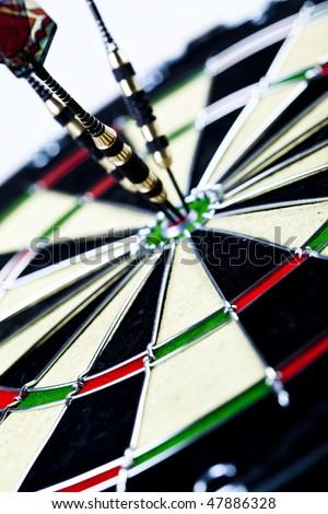 Dart on bulls eye target of dartboard - stock photo