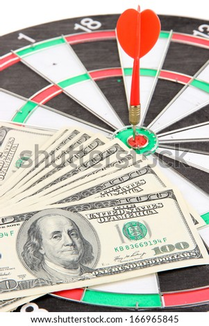 Dart on dartboard and money close up. Concept of success. - stock photo
