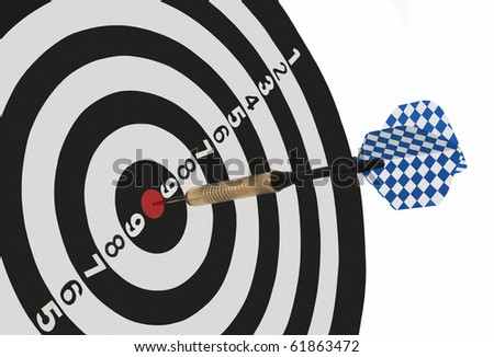 Dart On Target -- A dart sticks in the center of a target, a perfect bullseye - stock photo