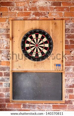 Dartboard on brick wall with chalk board score board and darts. - stock photo