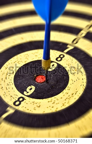 Dartboard target and blue dart arrow. Selective focus. - stock photo