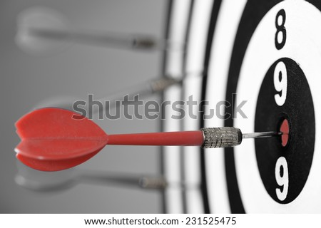 Dartboard with darts on gray background. - stock photo