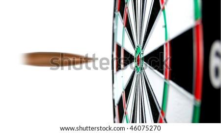 Dartboard with flight of bullet on the bullseye - stock photo