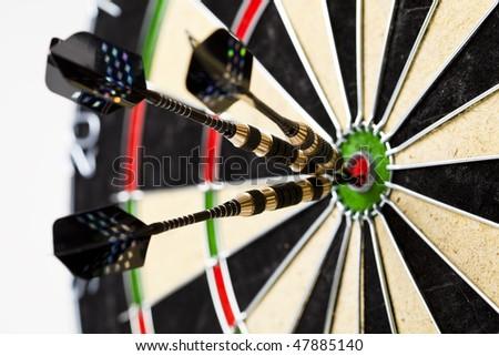 Dartboard with three darts in a bulls eye - stock photo