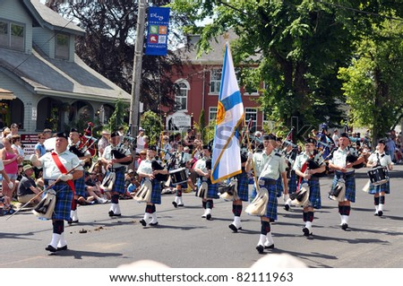 DARTMOUTH, CANADA - AUG 1:  A marching band, carrying a Nova Scotia flag and wearing the Nova Scotia tartan, marches in the 116th Natal Day Parade Aug 1, 2011 in Dartmouth, Nova Scotia.