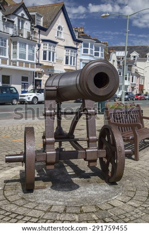 Dartmouth, Devon, UK, JUNE 4 2015 - Showing an old cast iron cannon sat next to a sea-side town, part of the town history due to the Britannia royal naval college which is also located in the town.