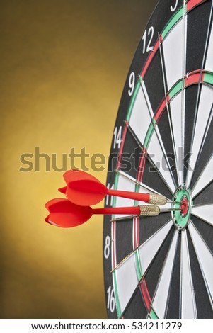 Darts arrows hitting the target center on a yellow background