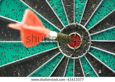 Darts board with single arrow in bullseye - stock photo