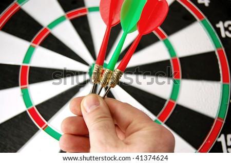 Darts in hand on dartboard background - stock photo