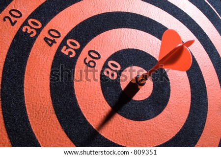 Dartsboard with arrow in center. - stock photo