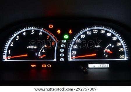 Dashboard dials illuminated at night in automobile - stock photo