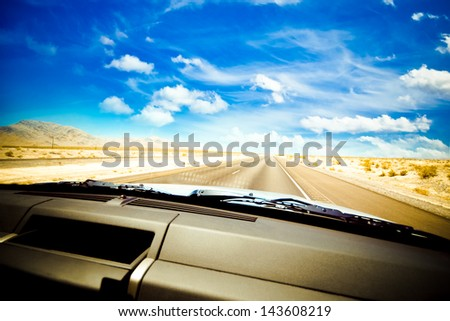 Dashboard seen while driving hot desert road - stock photo