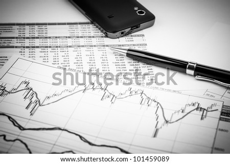 data analyzing in stock market: on the charts and quotes prints, the smart phone and a pen