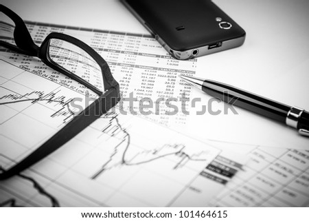 data analyzing in stock market: on the charts and quotes prints, the smart phone, eyeglasses and a pen