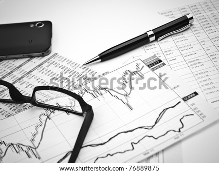 data analyzing in stock market: on the charts and quotes prints, the smart phone, eyeglasses and a pen - stock photo