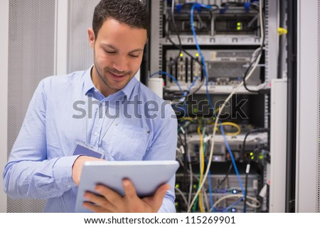 Data centre worker with tablet computer in data centre