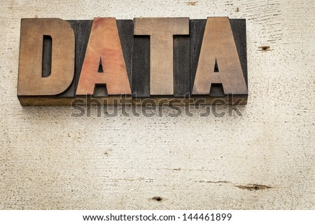 data word in vintage letterpress wood type on a grunge painted barn wood background