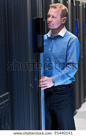 Datacenter administrator working on a large scale computer cluster. - stock photo