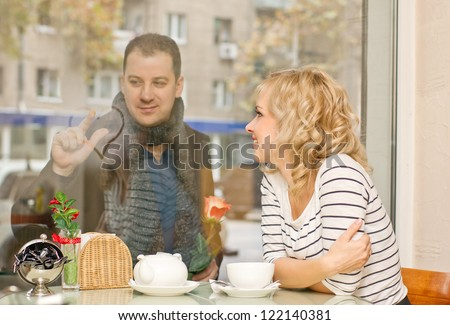 Date. Attractive young blond woman and her boyfriend at small cafe. Guy with rose draws a heart on the glass.