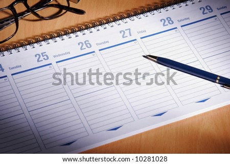 Date book on desk with glasses - stock photo