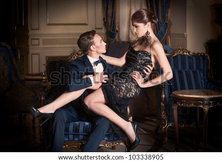 Date. Man in suit and woman in evening dress sitting on his lap - stock photo