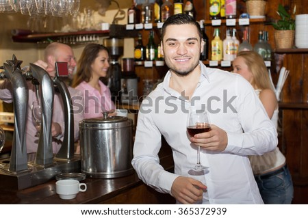 Date of positive couple drinking wine at bar and smiling - stock photo