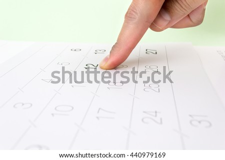 date on a calendar page with a finger pointing on it - stock photo