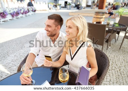 date, people, payment and finances concept - happy couple with wallet, credit card and wine glasses paying bill at restaurant - stock photo