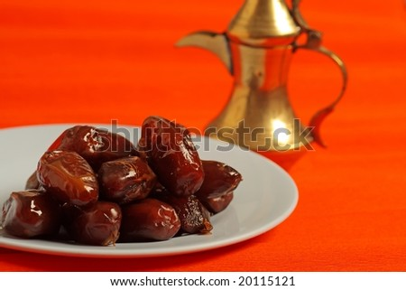 Dates and golden arabic teapot in the background - stock photo